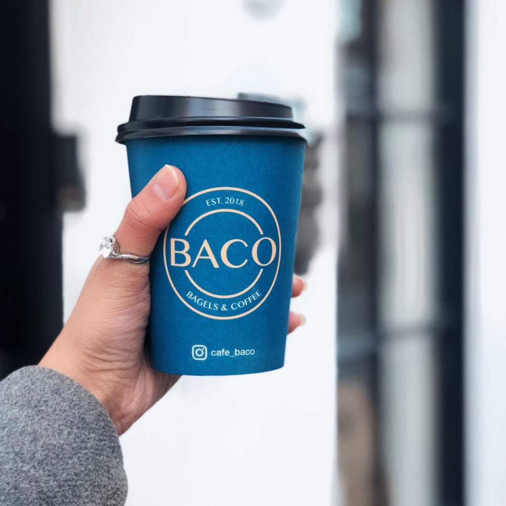 Female hand holding a cup of coffee from BACO - Bagles & Coffee